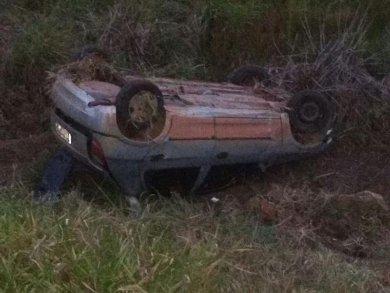 Carro parou com as rodas para cima ás margens de um açude.