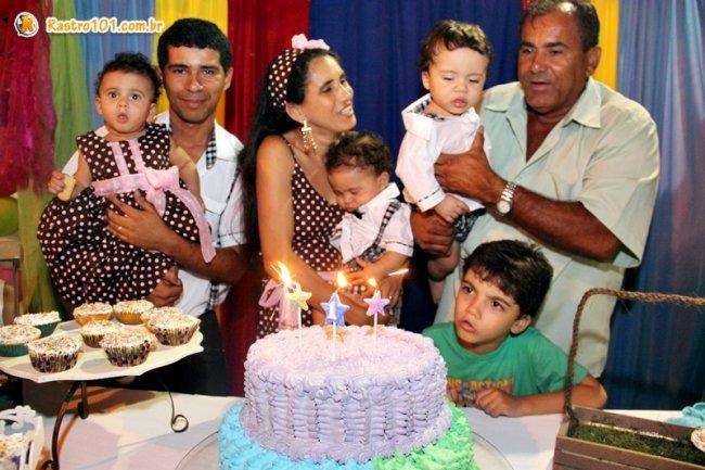 Olinto e Cristiane precisaram da ajuda do vovô para segurar um dos bebes ao apagar as velas do bolo de aniversário. (Foto: Rastro101)